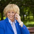 Portrait of an elderly beautiful woman talking on a cell phone — Stock Photo #79148590