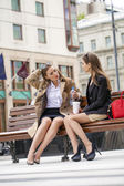 Young girlfriends sitting on a bench in the town center — Stock Photo