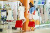 Two young beautiful girls standing at the storefront — Stock Photo