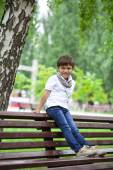 Little boy sitting on a bench in a summer park — Stock Photo