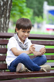 Little boy intently playing games on smartphone — Stock Photo