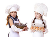 Two little girls in a white apron holding box of raw eggs and bo — Stock Photo