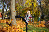 Happy woman drop up leaves in autumn park — Stock Photo