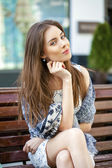 Brunette calm woman sitting on the bench in summer street — Stock Photo