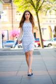Beautiful young girl in white dress walking summer street — Stock Photo