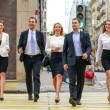 Team of five business people confidently striding along the summ — Stok fotoğraf #83892500