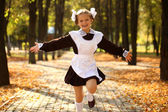 Happy little schoolgirl go home from school — Stock Photo