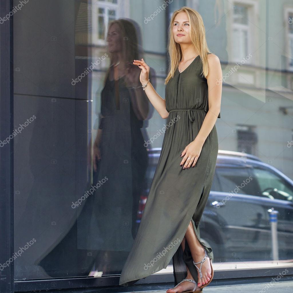 Unga vackra blonda kvinnan i långa gröna klänning poserar mot ...