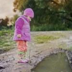 Cute little girl near a puddle — Stock Photo #63649505