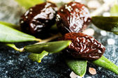 Sun-dried olives with green leaves — Stock Photo