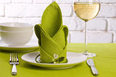 Green table setting with water liliy flowers — Stock Photo