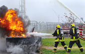 Two firemen fighting a large flame fire. — Stock Photo