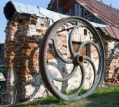 Large rusted metal industrial wheel against the background of an — Stock Photo