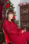 Beautiful adult woman listening music against Christmas tree — Stock fotografie