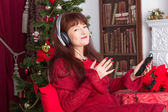 Adult woman listening music against Christmas tree — Stock fotografie