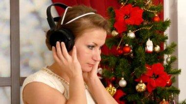 Beautiful adult woman listening music against Christmas tree — Stock Video