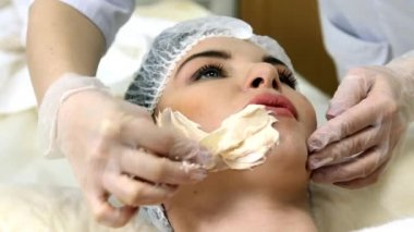 Applying facial mask at woman face at beauty salon — Stockvideo