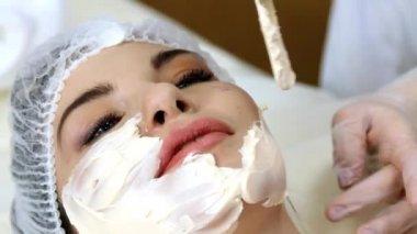 Applying facial mask at woman face at beauty salon — Stock Video