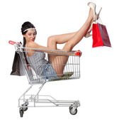 Pretty brunette woman sits in an empty shopping trolley with a s — Stock Photo