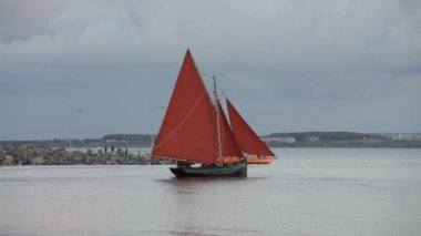Traditional wooden boat with red sail leaving Galway docks — Stock Video