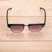 Occhiali da sole neri sul pavimento in legno — Foto Stock