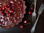 Chocolate tart with ganache and cherry. Dark style photo. — Stock Photo