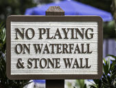 "Sign: ""No pling on waterfall & stone wall"" — Stock Photo"