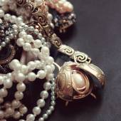 Art vintage golden and pearl bijouterie with scarab  on black si — Stock Photo