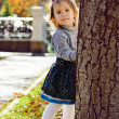 Girl hiding behind the tree — Stock Photo #52805549