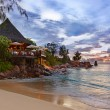 Cafe on Seychelles tropical beach at sunset — Stock Photo #52853653