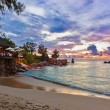 Cafe on Seychelles tropical beach at sunset — Stock Photo #73061727