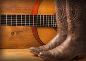 Country music with guitar and cowboy shoes — Stock Photo
