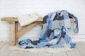 Patchwork quilt on rustic bench — Stock Photo
