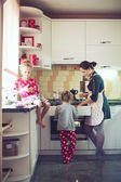 Mother with kids at the kitchen — Stock fotografie