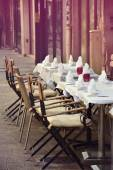 Romantic cafe terrace with empty tables and chairs on street in  — Stock Photo