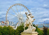 Marble statue and ferriw whell in Tuileries Garden (Jardin des Tuileries). Is  public garden located between Louvre Museum and Place de la Concorde in Paris, France — Stock Photo