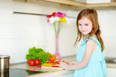 Girl helping  mother in   kitchen — Stock Photo