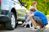 Family changing   car wheel — Stock Photo