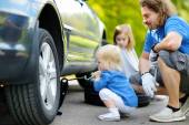 Girl helping father to change   car wheel — Stock Photo