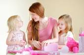 Mother and daughters with gift — Stock Photo