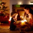 Mother and daughters near fireplace — Stock Photo #52247595