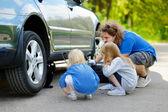 Family changing   car wheel — Stock Photo