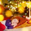 Girl sleeping under Christmas tree — Stock Photo #52801739