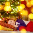Girl sleeping under Christmas tree — Stock Photo #52801875