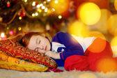 女孩睡在圣诞树下 — 图库照片