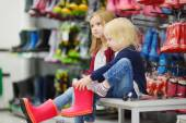 Sisters with new rain boots — Stockfoto
