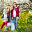 Mother and children in blooming garden — Stock Photo #61316565