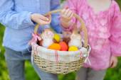 Little sisters with Easter eggs in basket — Stock Photo
