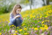 Girl in blooming dandelion flowers — Stock Photo