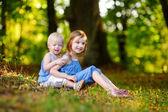 Little sisters having fun on grass — Stockfoto